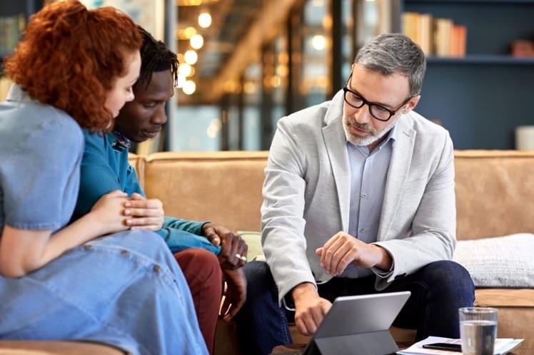 Personas en una mesa comparan las características de Finizens e Indexa Capital